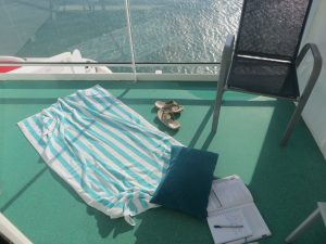 revising book and towel on balcony cunard queen victoria cruising isn't just for old people