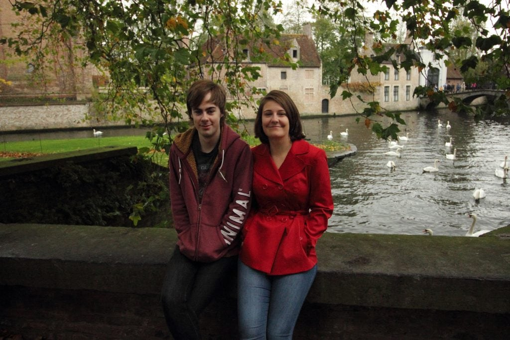 me and max in bruges girl in red coat and boy in front of canal in bruges