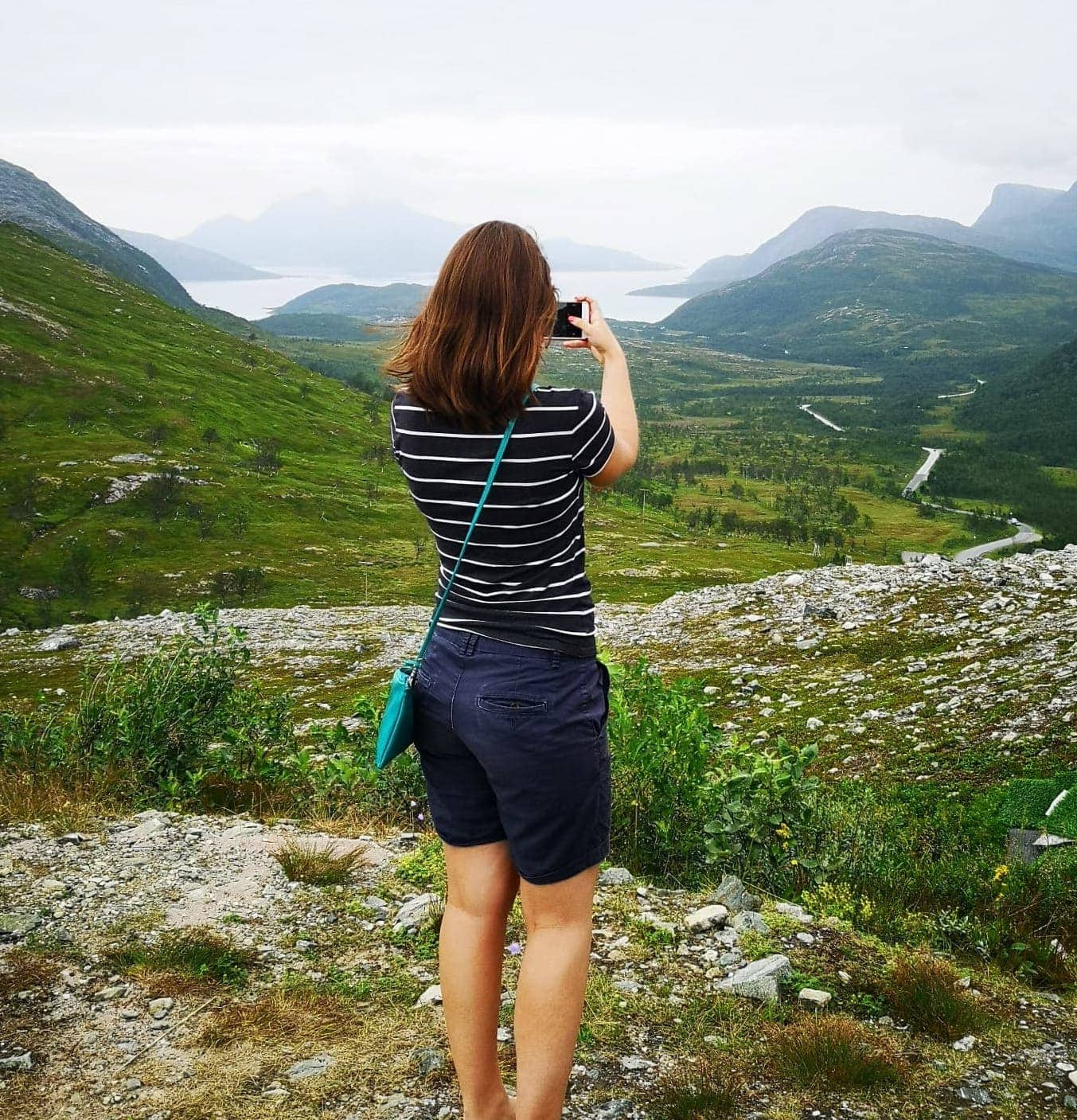 back of girl taking photo of view viking ocean cruises included excursions tromso