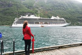 Viking Sea docked in Geiranger Emma Cruises Girl in red coat looking at cruise ship