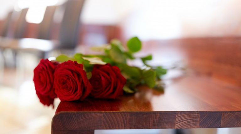 red roses on bench at funeral